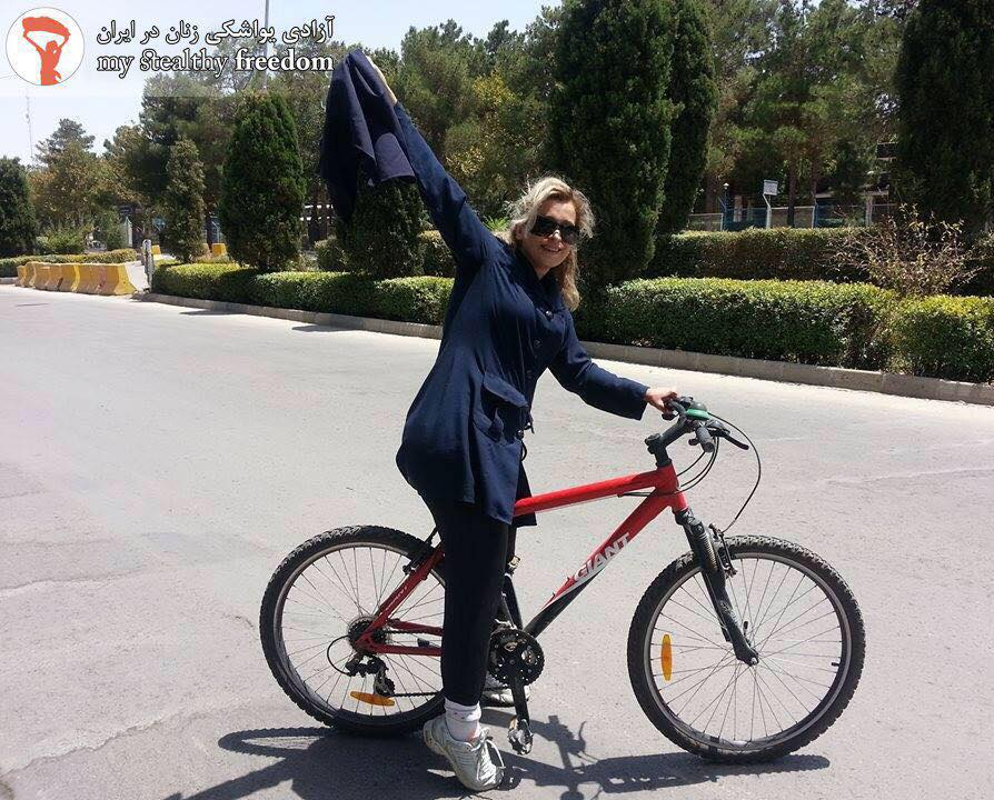 Iranian woman on a bicycle, waves her hijab